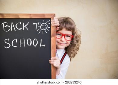 School kid in class. Happy child holding blackboard blank. Education concept