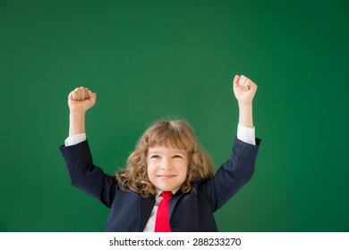 School kid in class. Happy child against green blackboard. Education concept. Winner, success