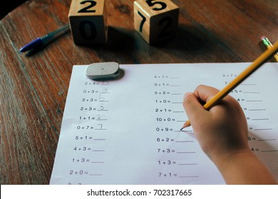 A school kid doing 1st Grade math homework.