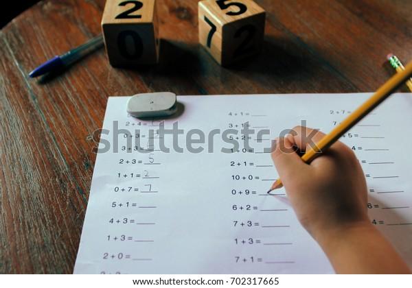 A school kid doing 1st Grade math homework.