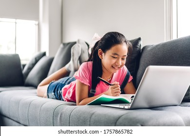 School kid little girl learning and looking at laptop computer making homework studying knowledge with online education e-learning system.children video conference with teacher tutor at home