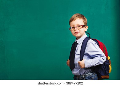 School, kid, rucksack. little Boy in eyeglasses. Cheerful smiling little kid with big backpack against chalkboard. Looking at camera. School concept. Back to School