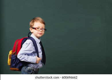 School, kid, rucksack. little Boy in eyeglasses. Cheerful smiling little kid with big backpack against chalkboard. Looking at camera. School concept. Back to School