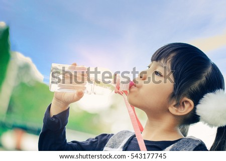 school kids drink water from a bottle against the background sky.