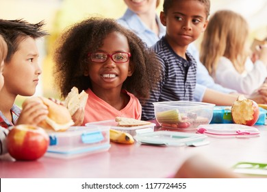 School kids eating packed lunches together at a table