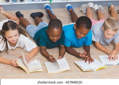 School kids lying on floor reading book in library at elementary school