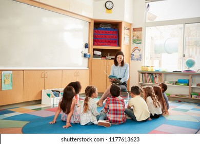 School kids sitting on the floor gathered around teacher