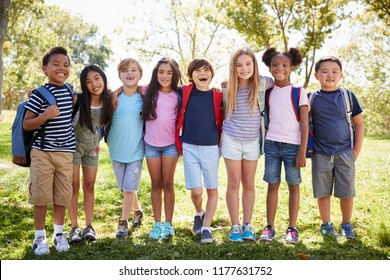 School kids stand embracing  in a row  outdoors, full length