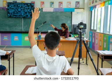 School kids wearing protective mask to Protect Against Covid-19,Group of school kids with teacher sitting in classroom online and raising hands,Elementary school,Learning and people concept.