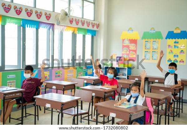 Schulkinder mit Schutzmaske zum Schutz vor Covid-19,Gruppe von Schulkindern mit Lehrer, die im Klassenzimmer sitzen und die Hände heben,Grundschule,Lernen und das Konzept der Menschen.