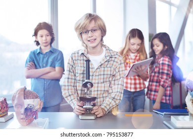 In school lab. Charming positive smart boy taking his turn for watching at the bacteria through the microscope while his classmates waiting in the line