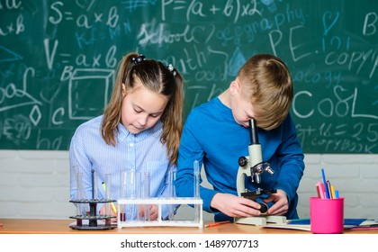 School laboratory. School education. Girl and boy communicate while conduct school experiment. Children studying together classroom. Chemical analysis. Kids study chemistry. School chemistry lesson.