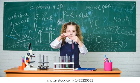 School laboratory. Girl smart student conduct school experiment. School pupil study chemical liquids. School chemistry lesson. Test tubes with substances. Formal education. Future microbiologist.