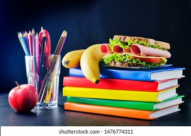 school lunch background with a sandwich, fresh fruits and multicolored books. toning. selective focus