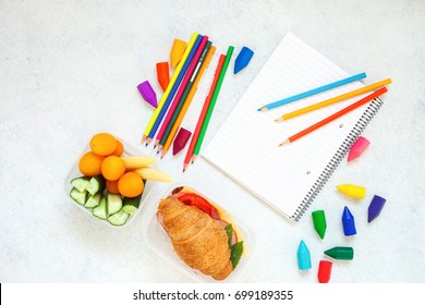 School lunch box with notebook and pencils on the light background. Top view/. Copy space