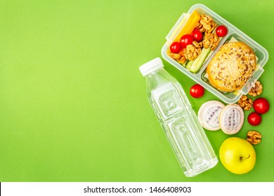 School lunch box with sandwich, fresh fruits, vegetables, water and nuts. Healthy eating habits for kids. Back to school concept. On bright green background, place for text, copy space, top view