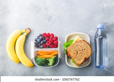 School lunch box with sandwich vegetables water almonds and fruits on black chalkboard