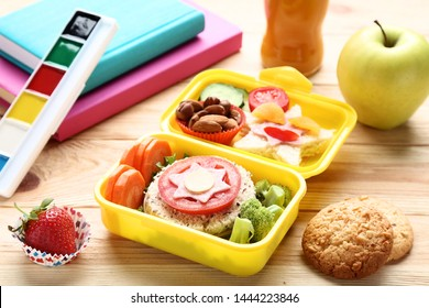 School lunch box with sandwich and vegetables on wooden table