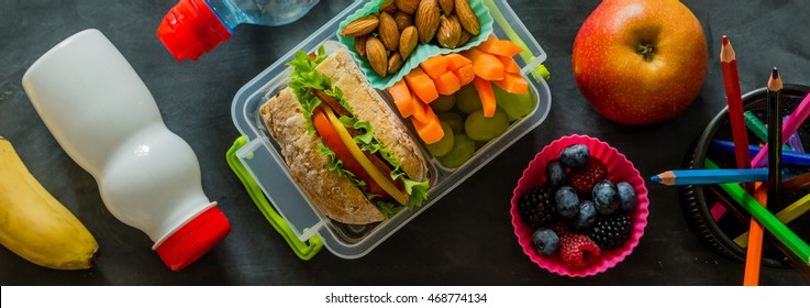 School lunch box with sandwich and vegetables, copy space