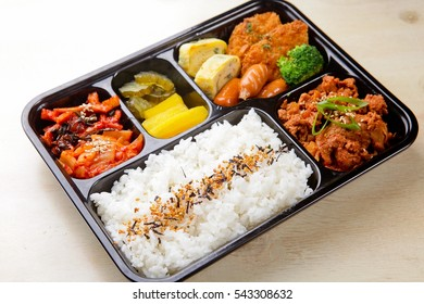 School lunch box with sandwich, vegetables, water, almonds and fruits on black chalkboard. Healthy eating habits concept