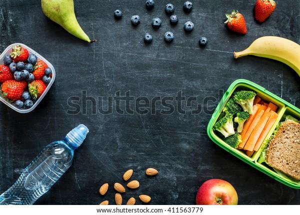 Schulessen mit Sandwich, Gemüse, Wasser, Mandeln und Obst auf schwarzem Karton. Gesunde Essgewohnheiten Konzept - Hintergrundlayout mit freiem Textraum. Flaches Legekomposition (Draufsicht).