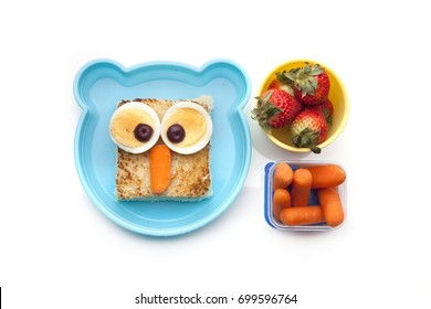 School lunch box snacks for kids over white background. Back to school. Healthy and fun snacks option for parents. Cute food art creative concepts. Bows with fruits and vegetables and cute sandwich.