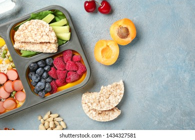 School lunch box with tasty food on color background