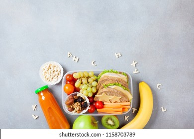 School lunch box with vegetables, fruits and sandwich on kitchen table top view.