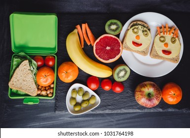 School lunch boxes with sandwich and fresh vegetables, nuts and fruits on blackbackground. Healthy eating concept.