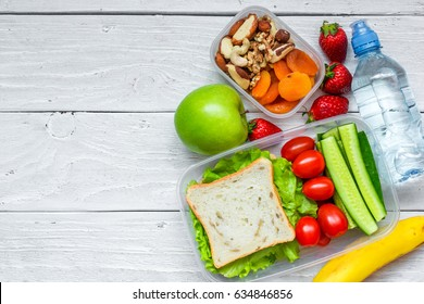 school lunch boxes with sandwich and fresh vegetables, bottle of water, nuts and fruits on white wooden background. healthy eating concept. top view with copy space