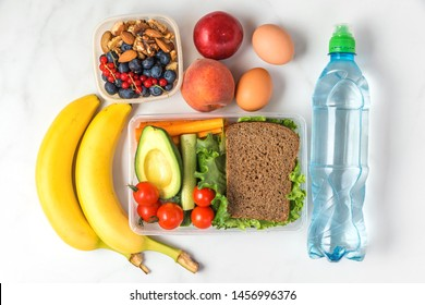 school lunch boxes with sandwich, vegetables, nuts, berries, banana, eggs, peaches and water on white marble background. top view