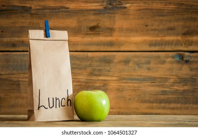 School lunch. Brown paper bag and a green apple on wooden background.
