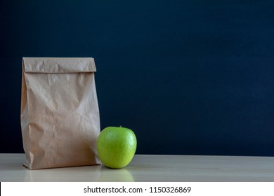 School lunch. Brown paper bag and  a green on blackboard background.