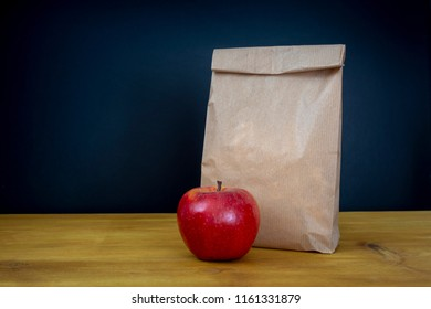 School lunch. Brown paper bag and a red apple on top of wooden desk