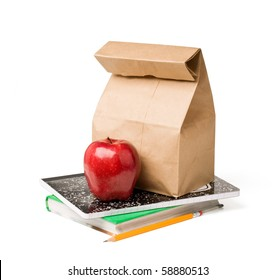 School lunch. Brown paper bag and a red apple on top of textbooks against white background.