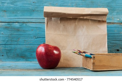 School lunch. Brown paper bag and a red apple on wooden background.