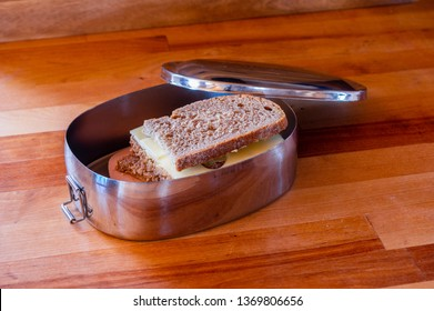 school lunch packed in stainless steel lunchbox on wooden surface