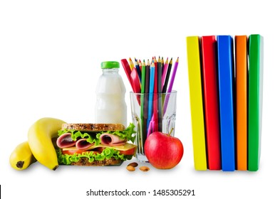 school lunch with a sandwich, fresh fruits and multicolored books on a white isolated background. toning. selective focus