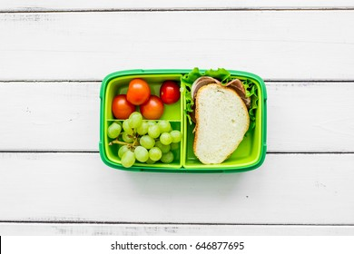 school lunch set with sandwich and vegetables in lunchbox background top view