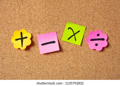 School maths concept. Sticky colorful notes in flower shape isolated with math symbols on cork board background.