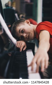 School of Music. musical education. the teenager plays the piano and looks at the keys.