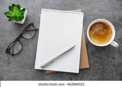 School notebook with glasses and coffee on table