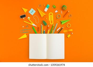 Schulheft und Schreibwaren auf orangefarbenem Tisch. Zurück zu abstraktem Schulhintergrund.