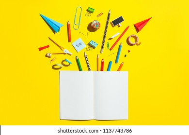 School notebook and stationery over yellow desk. Back to school abstract background.