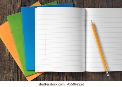 School notebooks and pencil on dark wooden table, top view