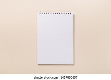 school notepad and pen on the beige desk. spiral notepad on a table