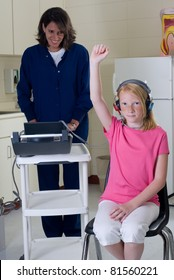 School nurse giving hearing test to student patient.