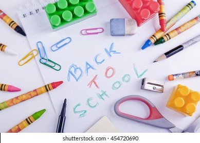 School objects: pen, pencils, crayons, rubber, scissors, paper clips and colorful blocks surrounding the note Back to School.