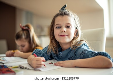 School obligations have to be done. Two little girls working homework at home. Space for copy. Focus on foreground. Looking at camera.