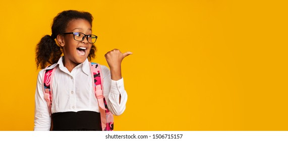 School Offer. Excited Black First-Grade Schoolgirl Pointing Thumbs At Copy Space On Yellow Background In Studio. Panorama